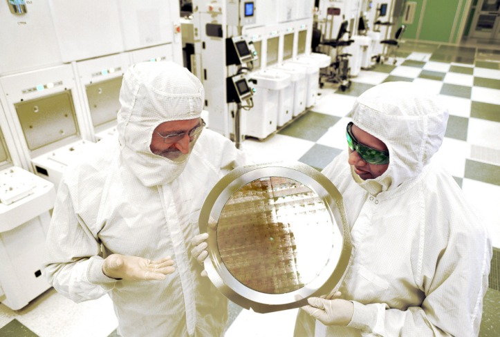 Dr. Michael Liehr (left) of SUNY Polytechnic Institute's Colleges of Nanoscale Science and Engineering and Bala Haran (right) of IBM Research inspect a wafer of 7nm test chips in a clean room in Albany.